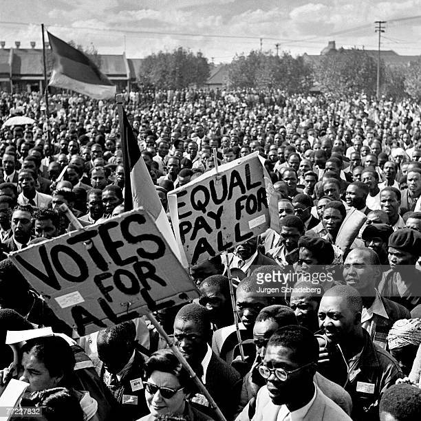 Crowds in Red Square in the Johannesburg suburb of Fordsburg South Africa with placards demanding equal pay and votes for all at an ANC rally held to...