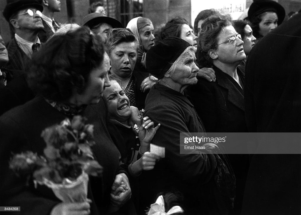 Crowds in Vienna waiting to greet homecoming prisoners show varying degrees of emotion ranging from stoicism to hysteria. In black and white book