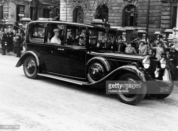 Crowds look on as Queen Mary is driven by in an official car, circa 1937.