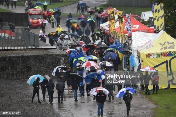Crowds make their way towards the exits as the start of the MotoGP race is delayed due to rain during the motorcycling British Grand Prix at...