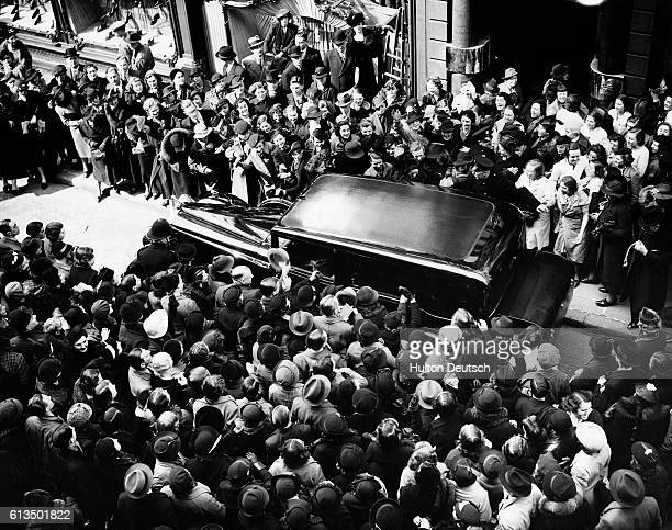 Crowds mob Queen Elizabeth's car as she leaves New Bond Street in London after a shopping visit for her Coronation Dress in 1937