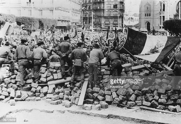 Crowds of Algerians who support the antiFrench antiindependence insurgents carry French flags and demonstrate before barricades manned by soldiers in...