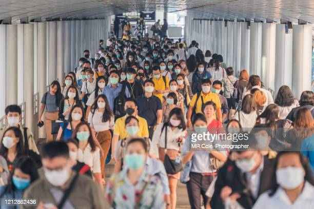 crowds of asian people wearing face protection while going to their workplace in bangkok at morning rush hour - spreading stock pictures, royalty-free photos & images