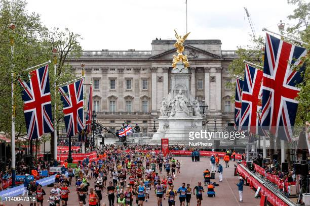 Crowds of athletes take the finishing straight in front of the Buckingham Palace during the Virgin Money London Marathon in London England on April...