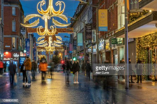 crowds of christmas shoppers in dublin city centre at henry street at dusk - henry street stock pictures, royalty-free photos & images