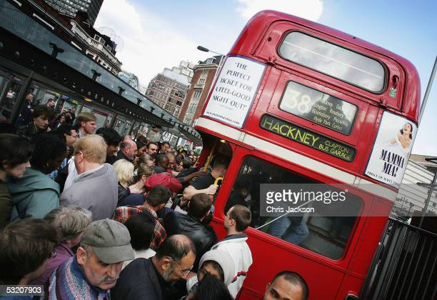 Crowds of commuters queue to get on one of the first buses to resume running as they make their way home following a series of blomb blasts which...