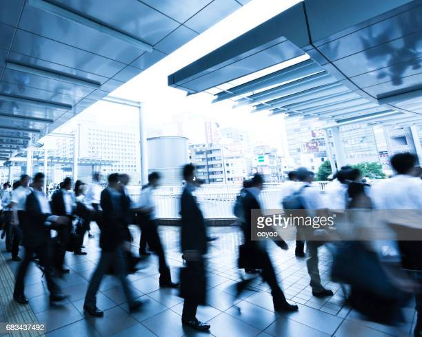 雨の朝に歩行者通路を歩く通勤者の群衆