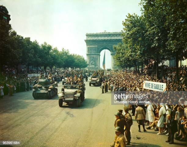 Crowds of French Patriots line Champs Elysees to view Allied Tanks and half tracks pass through the Arc du Triomphe after Paris, France was Liberated...