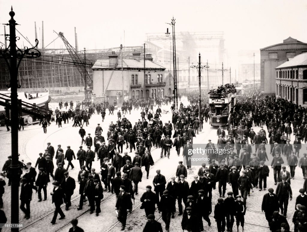 Crowds of men leaving the Harland and Wolff shipyard at Queen's Island in Belfast at the end of a shift in May 1911. In the distance the bow of the Titanic can be seen rising up above the rooftops beneath a huge gantry. At this time almost 4,000 men were engaged in the construction of the Titanic.