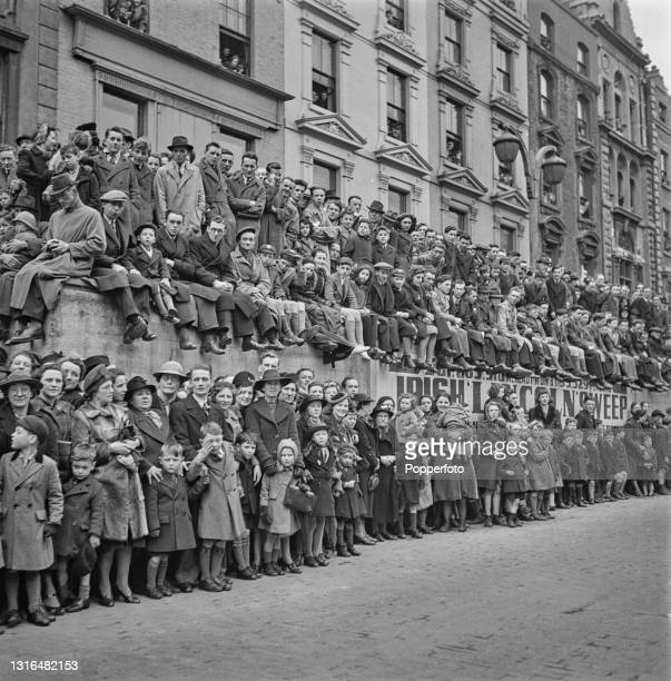 Crowds of men, women and children stand in front of and on a concrete air raid shelter to watch an inspection of Irish Army troops by Taoiseach Eamon...
