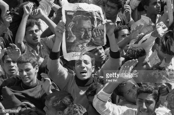 Crowds of mourners, most of them young men. Some carrying banners with the portrait of Gamal Abd al-Nasser in the streets of cairo during the funeral...