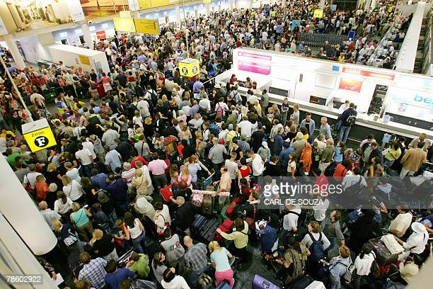Crowds of passengers are pictured in the Check In area of the South terminal at Gatwick Airport in Sussex in southern England 10 August 2006 Workers...