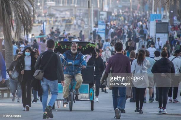 Crowds of people and a trishaw seen on Barceloneta beach promenade. The Barceloneta Beach in Barcelona is already crowded. Due to the corona virus...