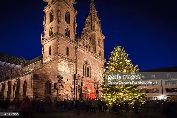 Crowds of people around illuminated Christmas tree by church, Basel, Switzerland