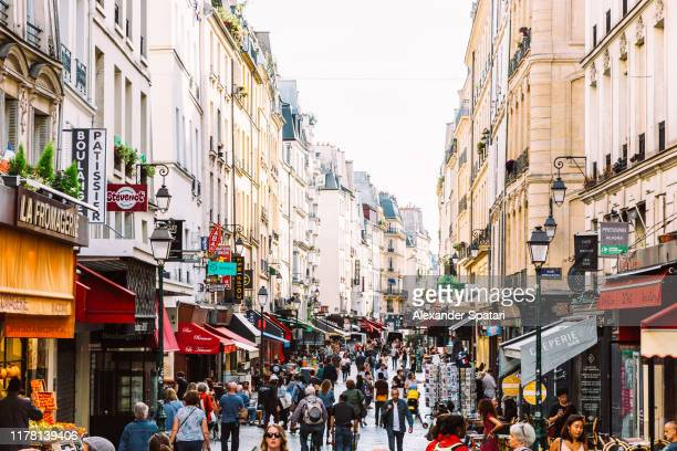 crowds of people at rue montorgueil pedestrian street in paris, france - pedestrian zone stock pictures, royalty-free photos & images
