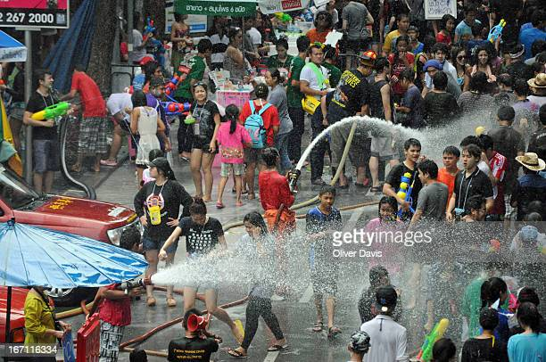 CONTENT] Crowds of people celebrating Songkran in a street in Si Lom Bang Rak district Bangkok Local city firemen are spraying jets of water at...