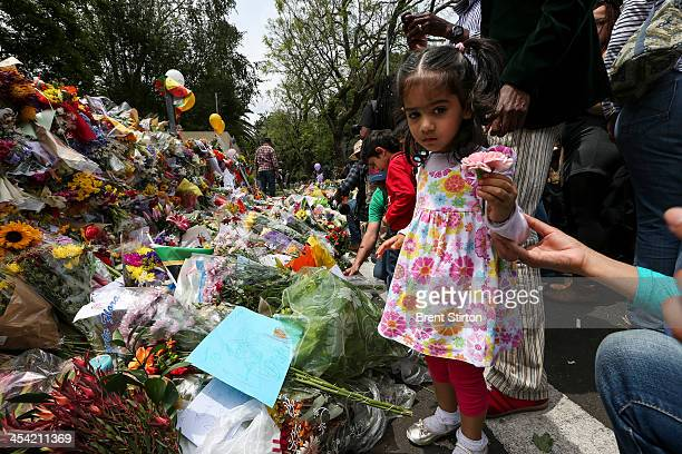 Crowds of people come to pay tribute to Nelson Mandela outside his Johannesburg home on December 7 2013 in Johannesburg South Africa Mandela also...