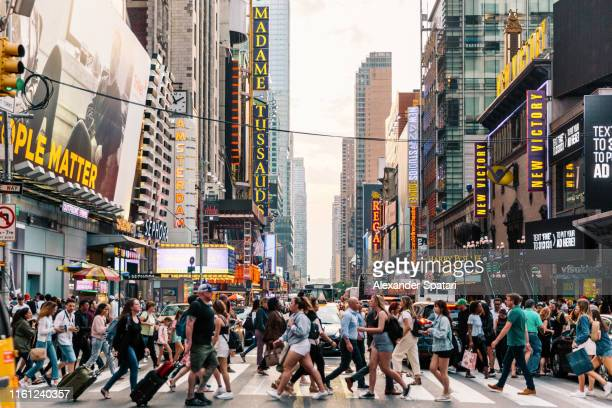 crowds of people crossing street on zebra crossing in new york, usa - new york city stockfoto's en -beelden