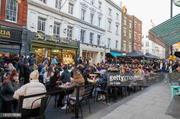 Crowds of people flock the outdoor restaurants and pub tables in Soho on April 12, 2021 in London, England. England has taken a significant step in...