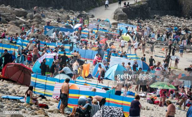 Crowds of people gather on the beach at Sennen Cove on August 1, 2021 in Cornwall, England. With international travel restrictions remaining likely...