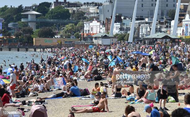 Crowds of people gather on the beach on a warm and sunny May Day bank holiday on May 25 2020 in SouthendonSea United Kingdom The British government...
