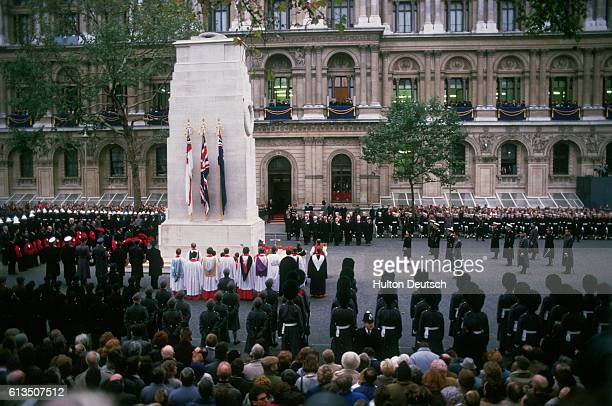 Crowds of people gather round the Cenotaph in commemoration of Armistice Day