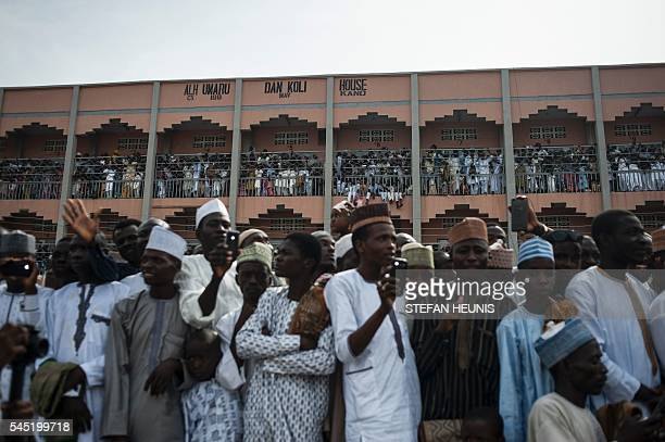 Crowds of people gather to see the Emir of Kano's procession passing during the Durbar procession in Kano northern Nigeria on July 6 2016 Kano is...
