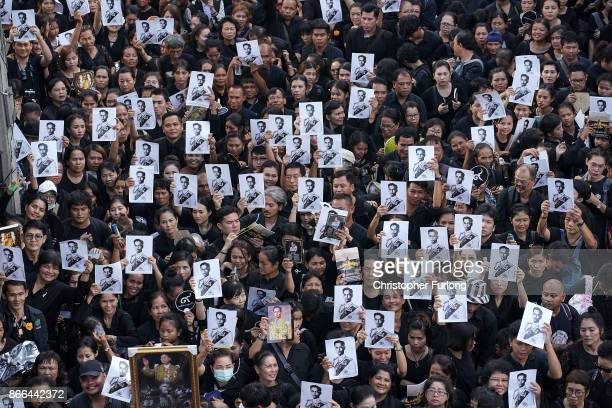 Crowds of people hold up a photograph of the late Thai King Bhumibol Adulyadej as they wait in line to attend his funeral on October 26 2017 in...