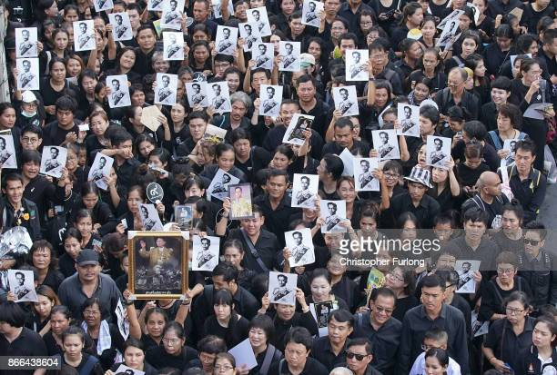 Crowds of people hold up photographs of the late Thai King Bhumibol Adulyadej as they wait in line to attend his funeral on October 26 2017 in...