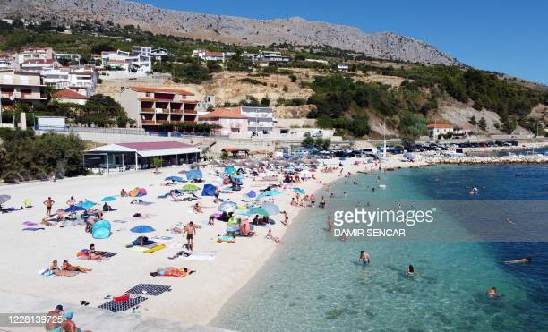 Crowds of people, including foreign tourists, enjoy the sun and the sea on August 21 in Split on the central Adriatic coast. - As United Kingdom...