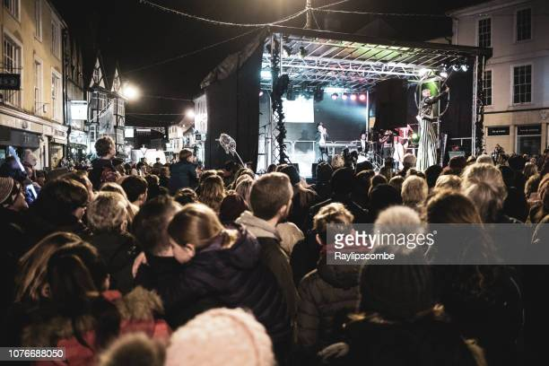 crowds of people looking at performers at the annual christmas advent market in cirencester, gloucestershire - cirencester stock pictures, royalty-free photos & images