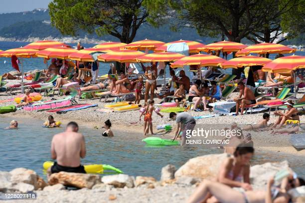 Crowds of people, mostly foreign tourists, sunbath and swim in the sea on August 13 in Crikvenica on the northern Adriatic coast. - On August 13, 180...