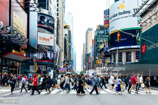 crowds of people on the street in new york city, ny, usa - new york state stock pictures, royalty-free photos & images