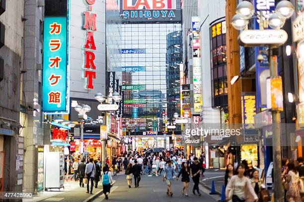 群衆の人々が都内の通りで夜