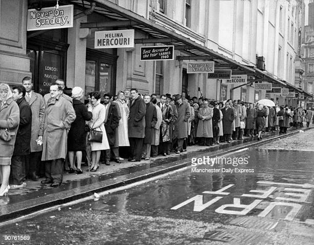 Crowds of people queueing outside the London Pavilion cinema in Leicester Square London to see the film 'Never on Sunday' staring the popular Greek...