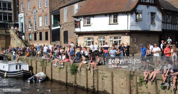 Crowds of people sit outside pubs and bars overlooking York's riverside. Daily life in Yorkshire, the largest county in England, UK.