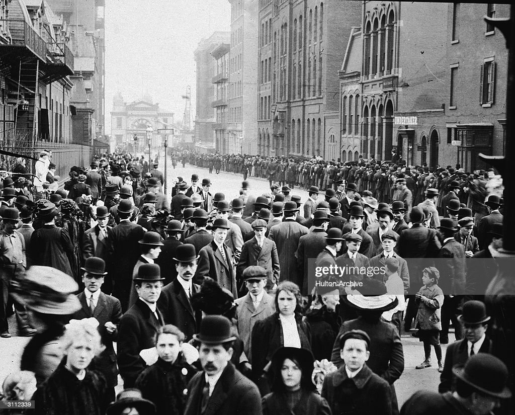Crowds of people stand in the street, waiting to identify bodies of immigrant workers following the Triangle Shirtwaist Company fire in New York City, March 25, 1911.