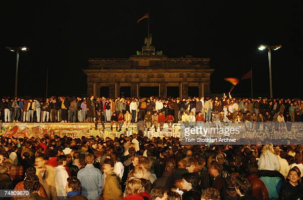 Crowds of people standing on and around the Berlin Wall on the West German side of the city at the time of the protests that led to the removal of...