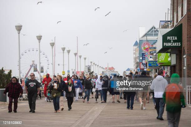 Crowds of people walk along the Ocean City Boardwalk during Memorial Day weekend on Sunday, May 24, 2020. Maryland recently lifted its stay-at-home...