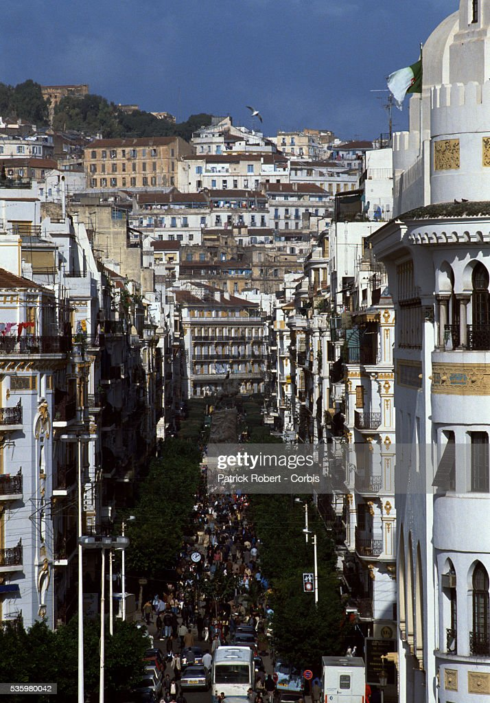 Crowds of people walk through a street in Algiers.
