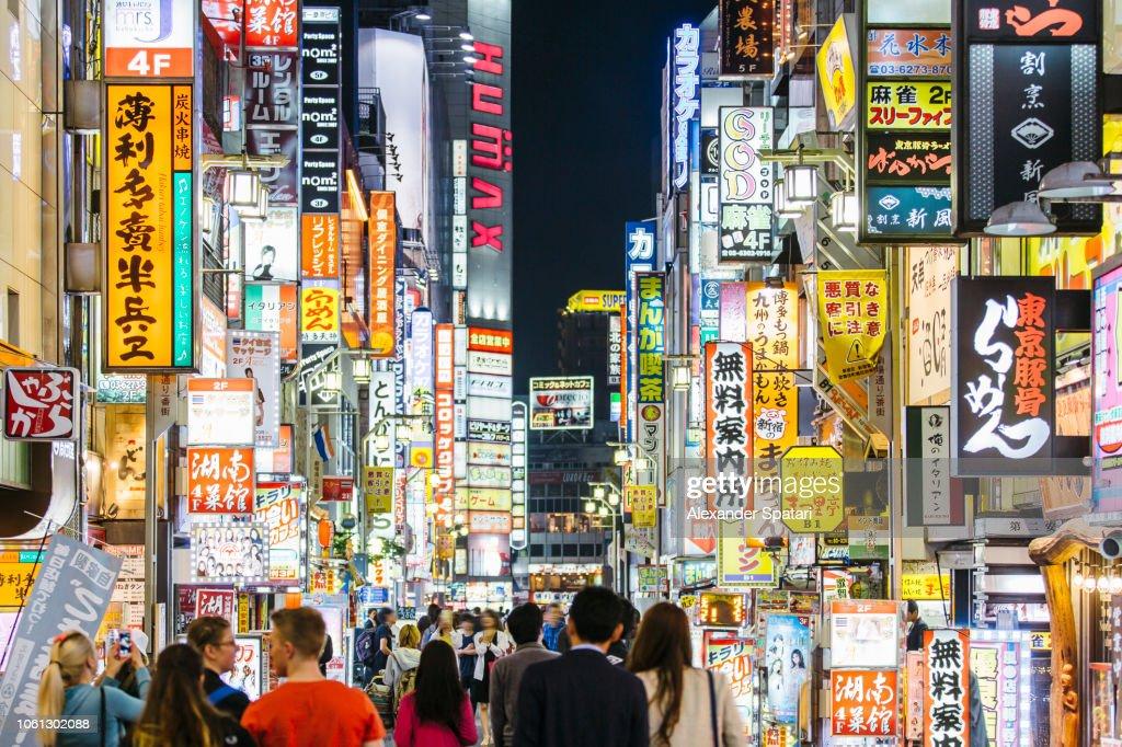 Crowds of people walking among illuminated neon signs at Kabukicho road in Shinjuku district, Tokyo, Japan : Stock Photo