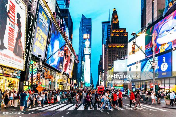 crowds of people walking at times square at night, new york, usa - new york state stock pictures, royalty-free photos & images