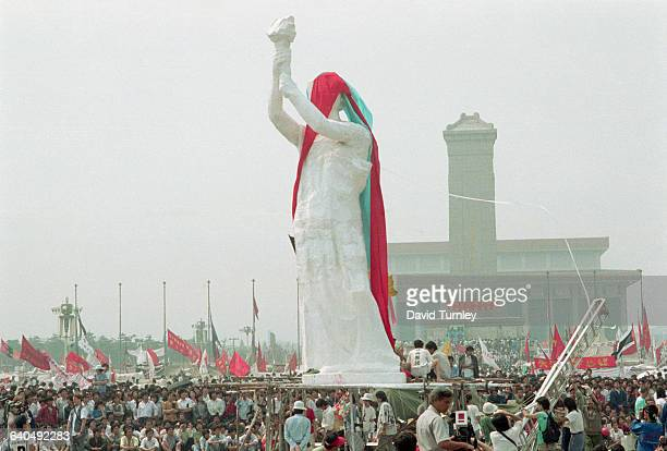 Crowds of people watch the unveiling of the Goddess of Democracy in Tiananmen Square The Monument to the People's Heroes and Mao Zedong Mausoleum are...