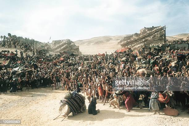 Crowds of people with their arms raised in the air in celebration in a scene from 'The Ten Commandments' 1956 The biblical epic was directed by Cecil...