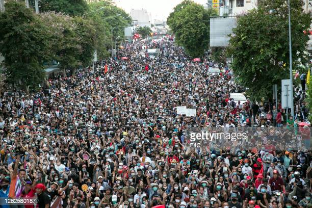 crowds of protesters march in bangkok, thailand - political rally stock pictures, royalty-free photos & images