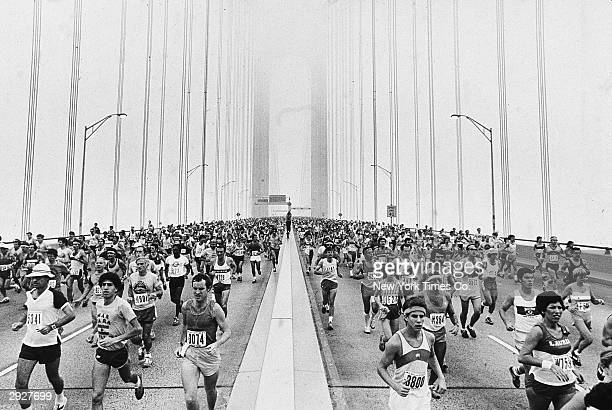 Crowds of runners run across the VerrazanoNarrows Bridge at the beginning of the New York City Marathon New York City October 21 1979