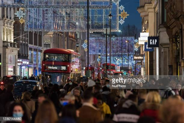 Crowds of shoppers and commuters walk along Oxford Street decorated with festive illuminations ahead of introduction of tougher coronavirus...