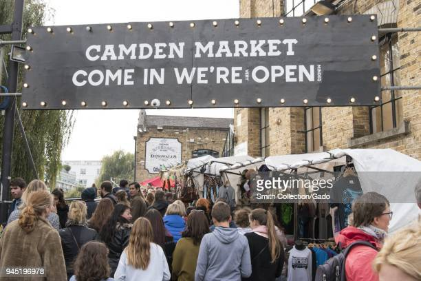 """Crowds of shoppers, passing under an entrance sign reading """"Camden Market Come in We're Open , """" and walking on a pedestrian street, lined with..."""