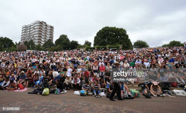 Crowds of spectators gather on 'Murray Mound' outside Centre Court to watch Marin Cilic of Croatia in action against Roger Federer of Switzerland on...