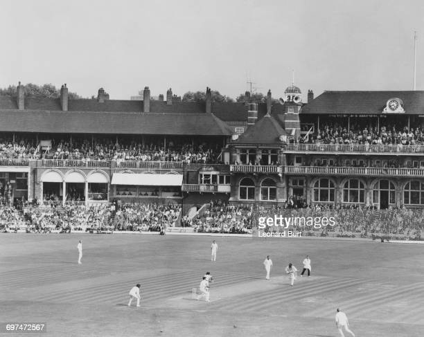 Crowds of spectators in the grandstand and the Oval Pavilion look on as Alvin Kallicharran and Clive Lloyd of the West Indies run between the wickets...